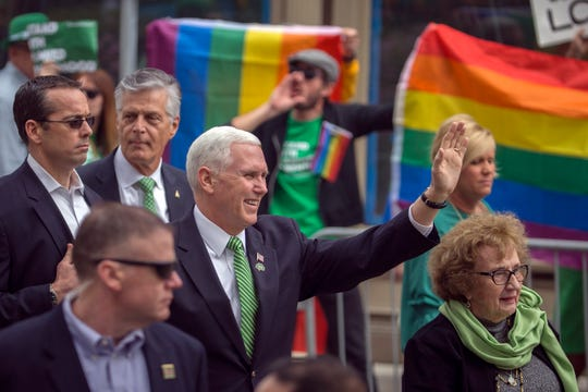 Vice President Mike Pence and his mother Nancy Pence Fritsch, right, wave while walking in the St. Patrick's Day parade March 17, 2018, in Savannah, Ga. Some protesters followed Pence.