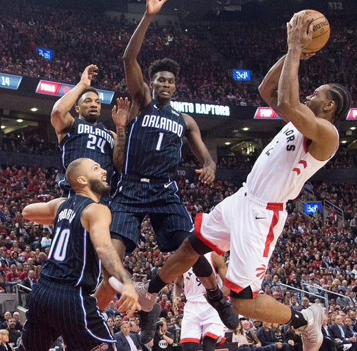 April 16: Raptors forward Kawhi Leonard drives to the basket and shoots over three Magic players during Game 2. Leonard scored 37 points in the 111-82 win.