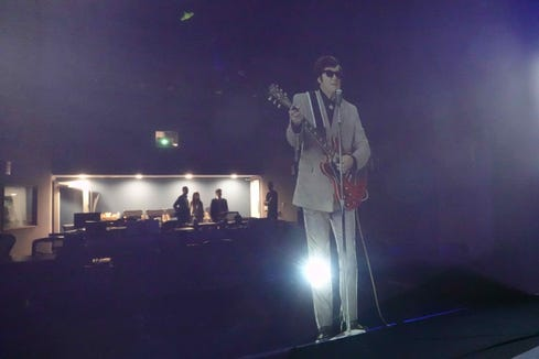 Taking a look at a hologram of Roy Orbison from behind a video screen