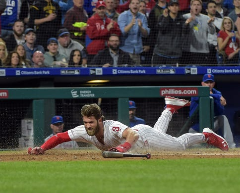 April 16: The Philadelphia Phillies' Bryce Harper slides into home plate during the first inning against the New York Mets at Citizens Bank Park. The Phillies scored 10 runs in the first inning en route to a 14-3 win.