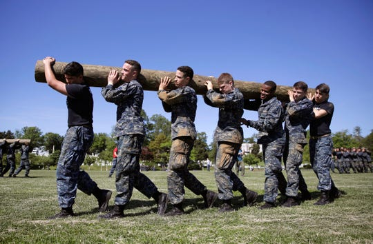 First-year midshipmen carry a log during Sea Trials, a day-long training exercise that caps off their plebe year at the U.S. Naval Academy in Annapolis, Md., May 16, 2017. The academy on April 15, 2019 confirmed it will not accept transgender students beginning with the 2020 school year.