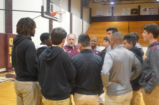 Alan Tinsley (center) talks to members of the Grant boys basketball team. Tinsley was introduced as the Cougars new coach Wednesday.