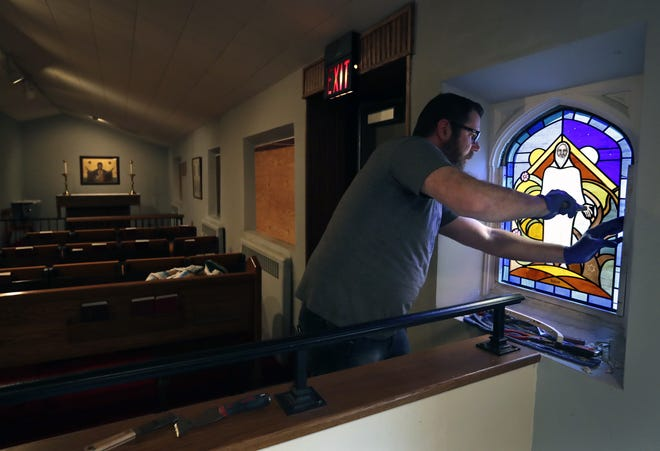Russell Farlow, a glazier with Coventry Glassworks and Gallery helps re-install a stained glass window at All Saints Episcopal Church in Appleton after a vandalism attack last month.