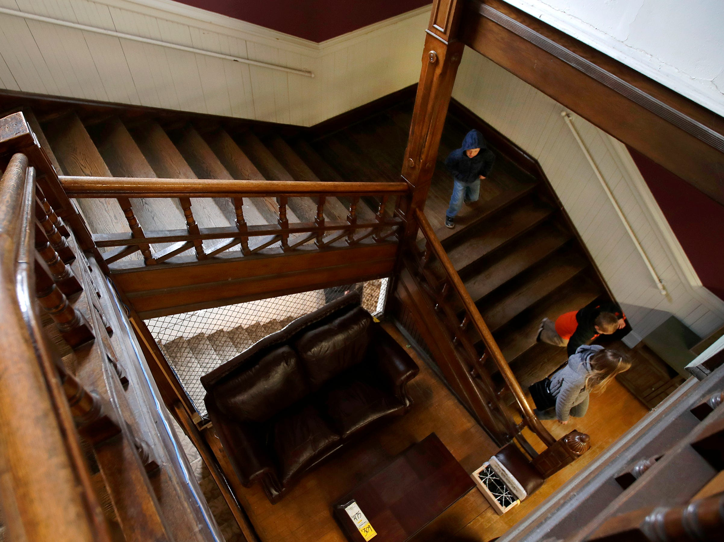 Kayla Hendricks, of Appleton, walks down the grand staircase in Gabriel Furniture with her sons Charlie, 5, and Bennett, 3, while looking around the building Thursday, April 18, 2019, in Appleton, Wis. Hendricks used to visit the building, which was built in 1888, as a child. The staircase is original to the building.