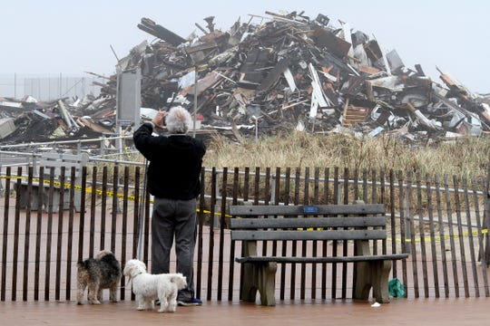 A man takes photos of the debris pile left behind Monday morning, April 15, 2019, after a Saturday fire destroyed the pavilion on the north end of the Ocean Grove boardwalk.