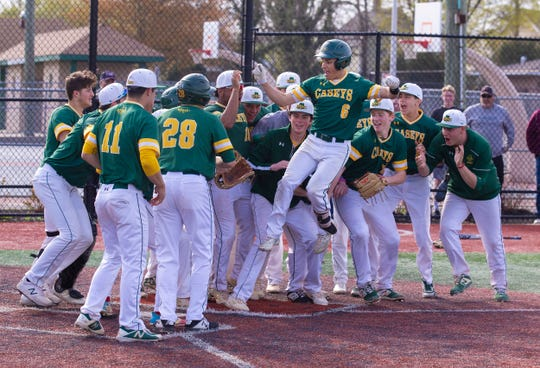 Red Bank Catholic players greet team mate Alex Gonzalez at the plate after Gonzalez homered in the bottom of the third inning for Red Bank Catholic's lone run in its 1-0 win over Manasquan