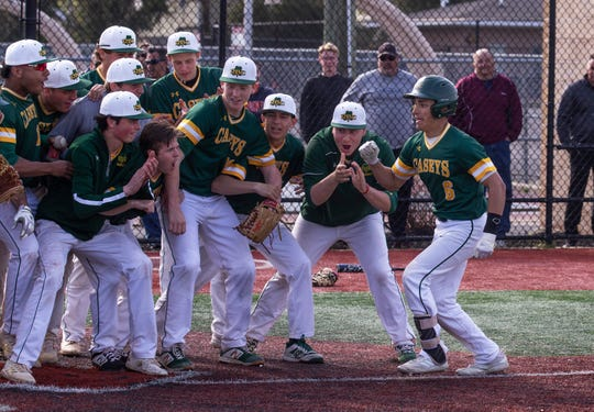 Red Bank Catholic players greet team mate Alex Gonzalez at the plate after he hit his home run. Manasquan baseball vs Red Bank Catholic in Red Bank, NJ on April 18, 2019.
