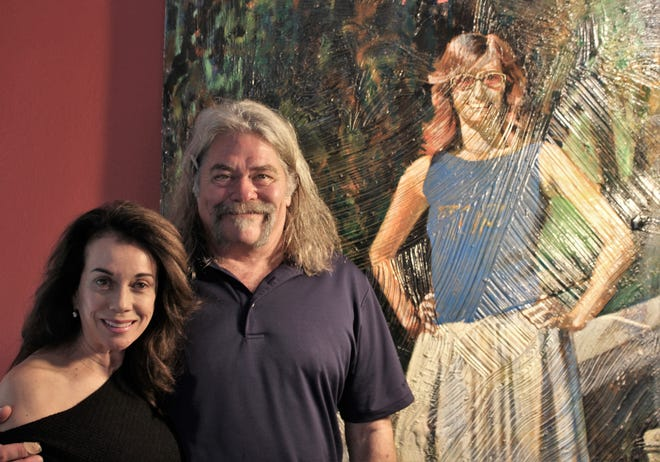 Cindy Vest and Matt Aston, near a large painting of his of a writer friend commissioned for an event in Los Angeles that's now in his studio in Abilene.