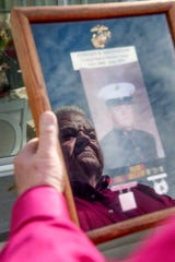 Stephen Henderson, a Marine Corps combat veteran of the Vietnam War, holds a photograph and military medals at his home in Fairview April 18, 2019.