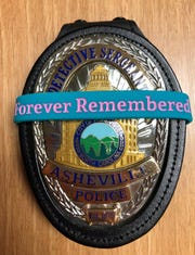An Asheville Police Department badge wrapped in a bracelet in remembrance of Erica Smith and her children Keithan Whitmire and Harmony Smith, all of whom were fatally shot a year ago.