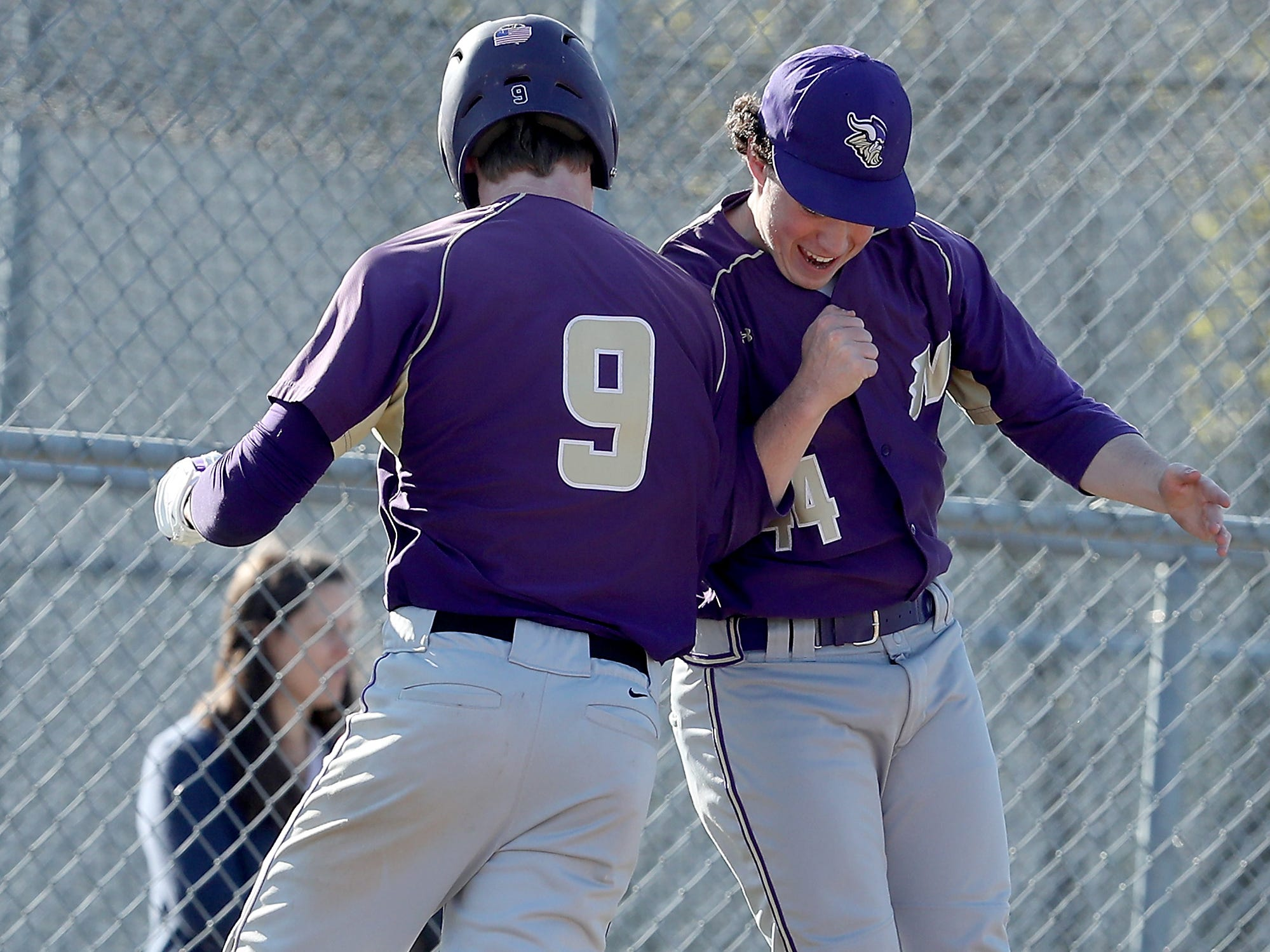 North Kitsap's Chris Schuchart (9) and Andrew Jones (44) leap into the air in celebration of Schuchart's home run hit against Bremerton on Wednesday, April 16, 2019.