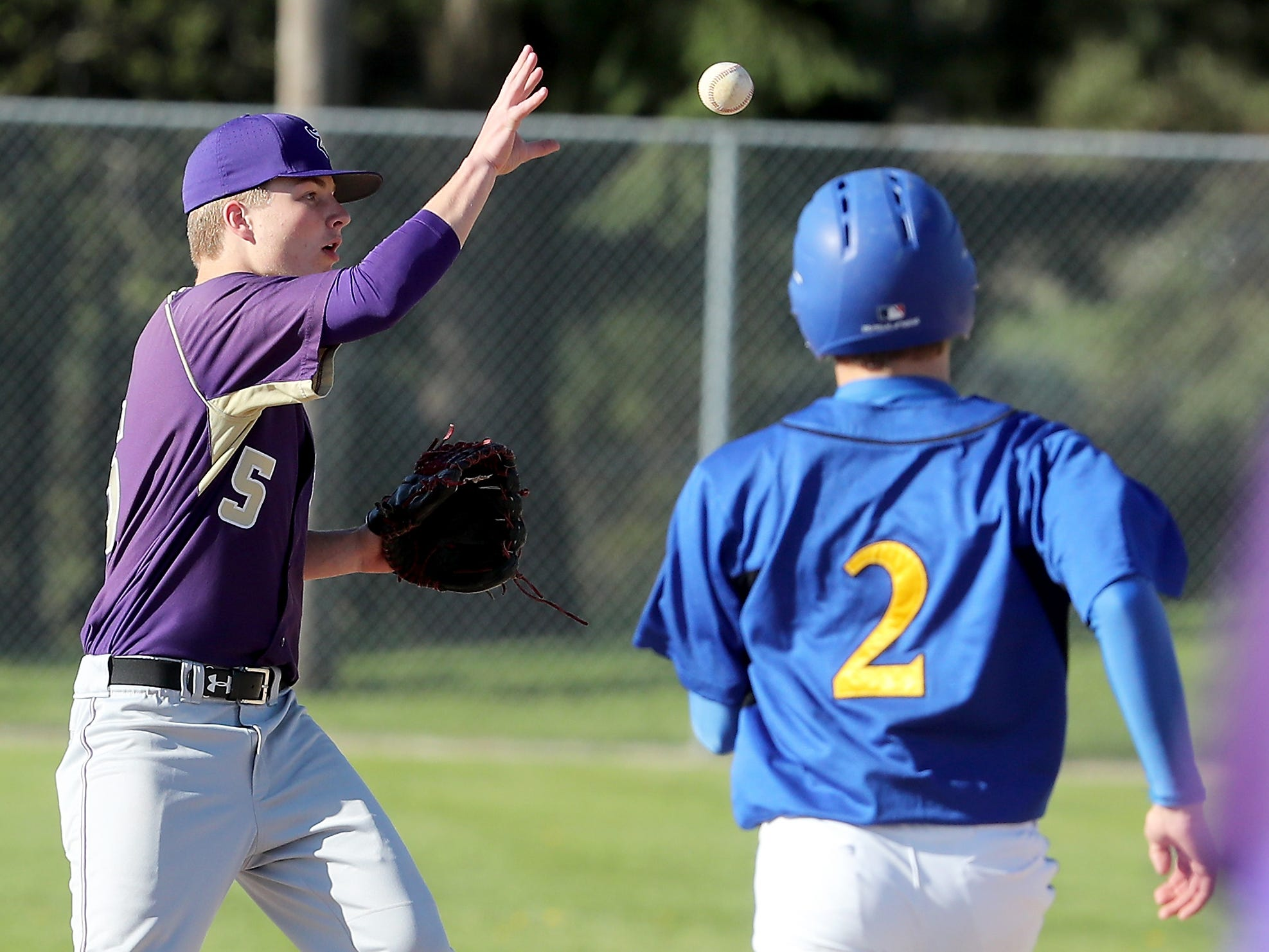 North Kitsap's Colton Bower (5) makes a catch at second and Bremerton's Hunter Tipler (2) is out on the play at Bremerton's Legion Field on Wednesday, April 16, 2019.