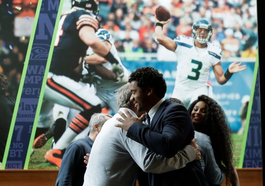 Seattle Seahawks quarterback Russell Wilson, center, hugs head coach Pete Carroll, left, in front of a photograph of Wilson in action, as Wilson's wife Ciara looks on at right, Wednesday, April 17, 2019, prior to a NFL football press conference in Renton, Wash. Earlier in the week, Wilson signed a $140 million, four-year extension with the team.