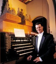 Lee Gwozdz sits at the Corpus Christi Cathedral Organ in the 1990s. That decade, Gwozdz also played the Choir Organ at the Notre Dame Cathedral in France.