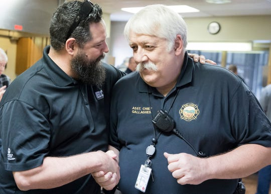 Steve Gallagher, right, is congratulated by Jason Knight from B&C Communications during a surprise retirement party at the Chillicothe Fire Department on April 18, 2019.