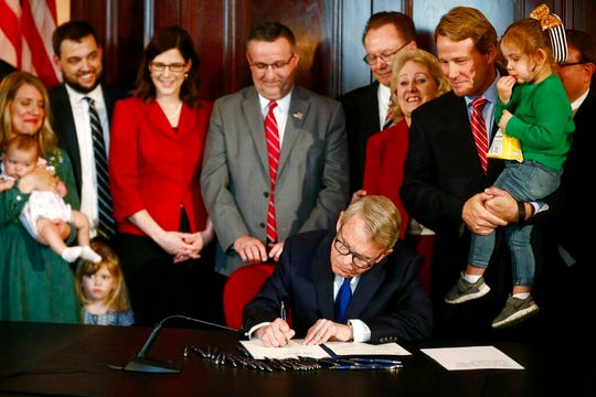 Gov. Mike DeWine speaks before signing a bill imposing one of the nation's toughest abortion restrictions, Thursday, April 11, 2019 in Columbus, Ohio. Lt. Governor Jon A. Husted stands at right holding Faye Zaffini, 2, the daughter of his chief of staff. DeWine's signature makes Ohio the fifth state to ban abortions after the first detectable fetal heartbeat. That can come as early as five or six weeks into pregnancy, before many women know they're pregnant. (Fred Squillante/The Columbus Dispatch via AP)