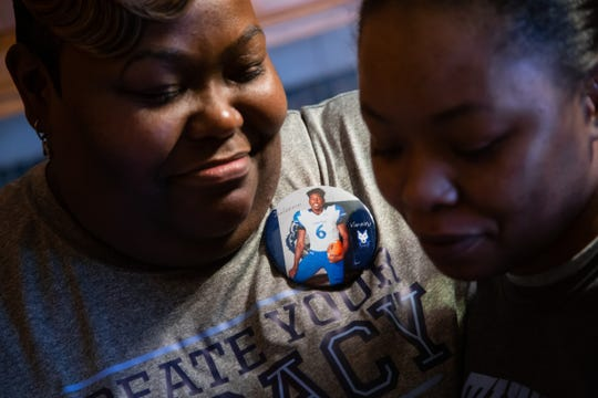 Melvenna Fant-Jones (left), 36, wears a button of her son Lakeview High School senior Delorean Ishmon II at her home in Eastpointe while talking with Jacqueline Fant after attending his signing of letter of intent to attend and play football at Northwood College on Friday, March 8, 2019.