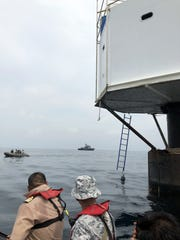 Thai naval officers inspecting a a floating dwelling in the Andaman Sea.