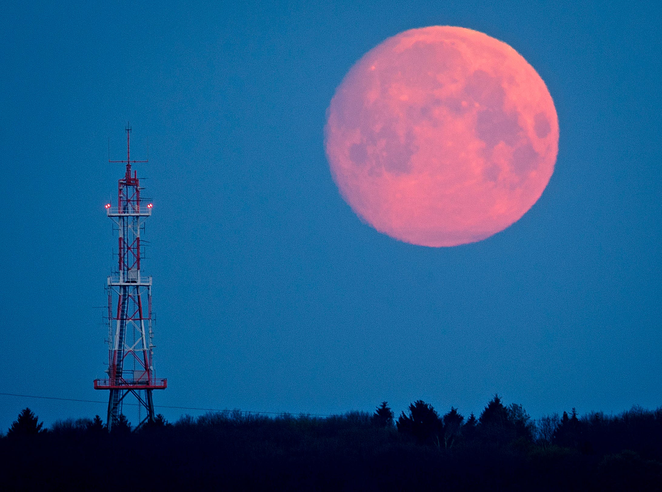 The moon goes down over the Taunus mountains near Frankfurt, Germany, early Thursday, April 18, 2019.