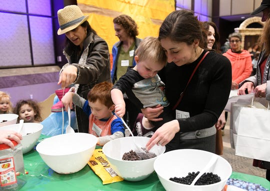 """Shaye Nielsen of Wolverine Lake holds her son, Eli Nielsen, 2, while she makes """"manna trail mix"""" with her other son, Marcus Nielsen, 4, left, at Matzah Factory Extravaganza at the Jewish Community Center in West Bloomfield."""