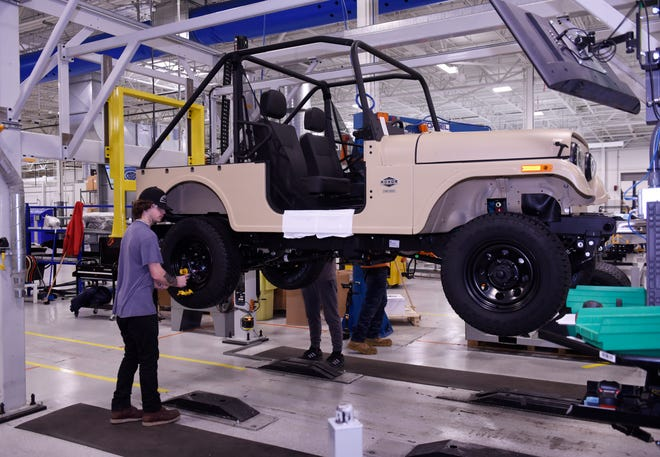 Jacob Myers installs wheels on a Mahindra Roxor off-road utility vehicle at Mahindra's Auburn Hills plant. The India-based vehicle maker and Ford Motor Co. will co-develop a midsize SUV for sale in India and emerging markets.