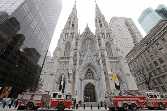 While firemen conduct an inspection, fire trucks are parked in front of St. Patrick's Cathedral in New York, Thursday, April 18, 2019.
