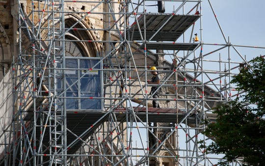 A man works on the scaffolding on the facade of the Notre Dame Cathedral in Paris, Thursday, April 18, 2019.