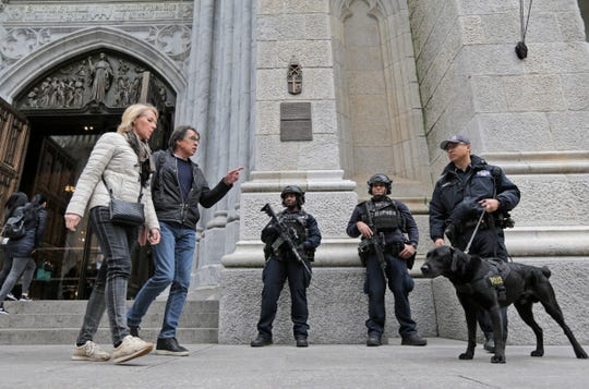 Tourists walk past police officers standing in front of St. Patrick's Cathedral in New York, Thursday, April 18, 2019.