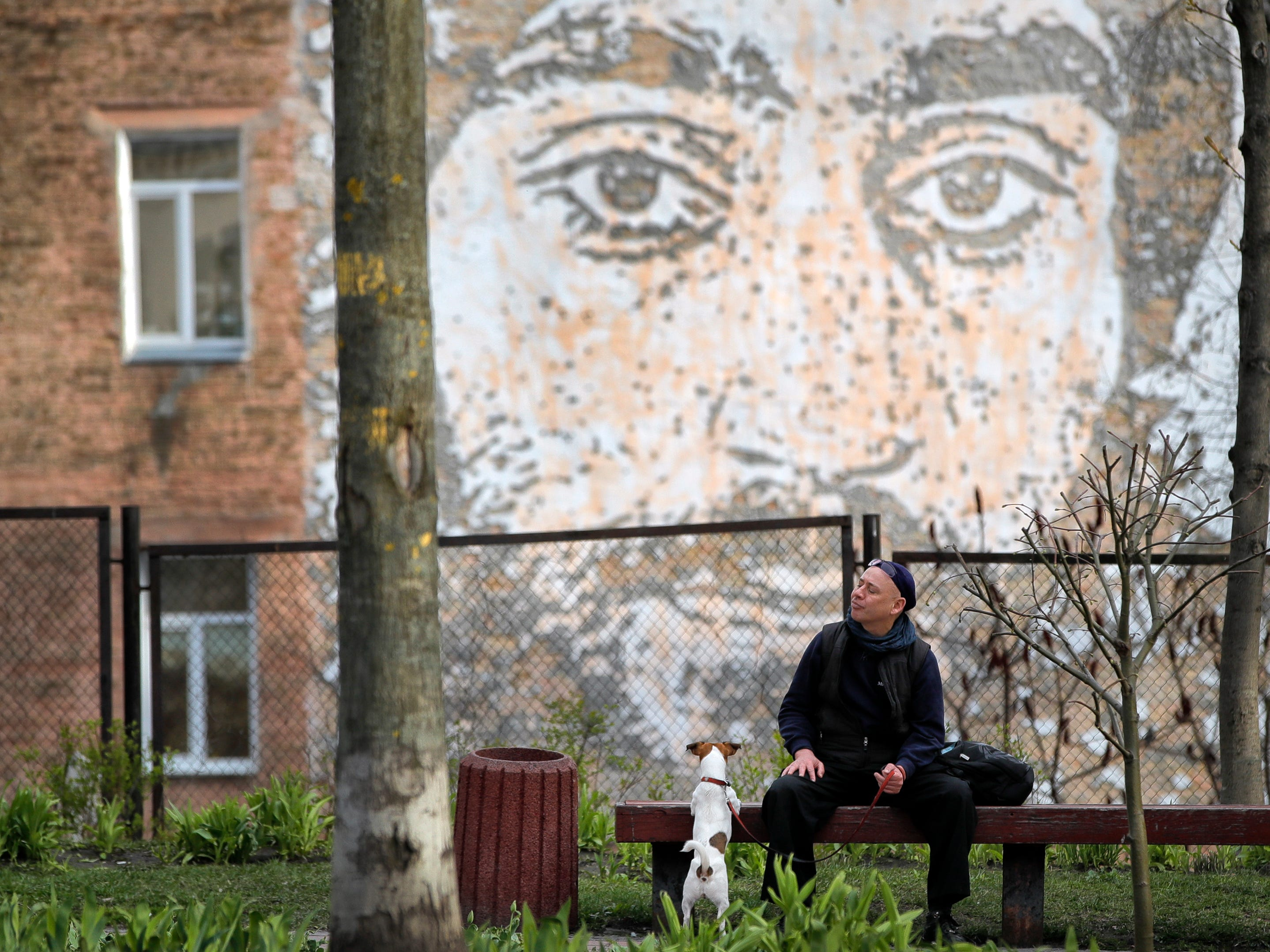 A man walking a small dog pauses on a bench in Kiev, Ukraine, Thursday, April 18, 2019. The second round of presidential vote in Ukraine will take place on April 21.