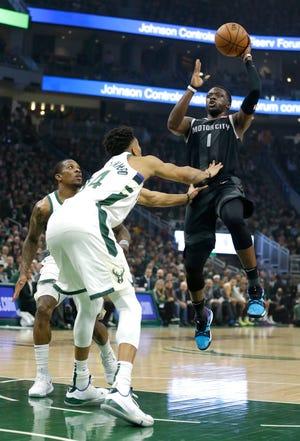 Pistons guard Reggie Jackson (1) shoots against Milwaukee Bucks' Giannis Antetokounmpo during the first half of Game 2 on Wednesday in Milwaukee.