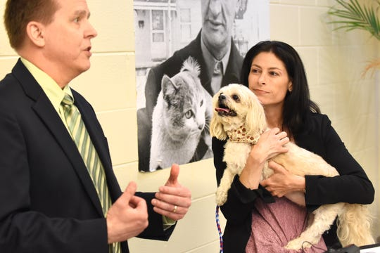 Michigan Attorney General Dana Nessel holds Gucci, a 10-year-old Shi Tzu, as she listens to Consumer Protection Bureau Chief Joseph Potchen speak about the importance of recognizing and stopping puppy scams in the state.