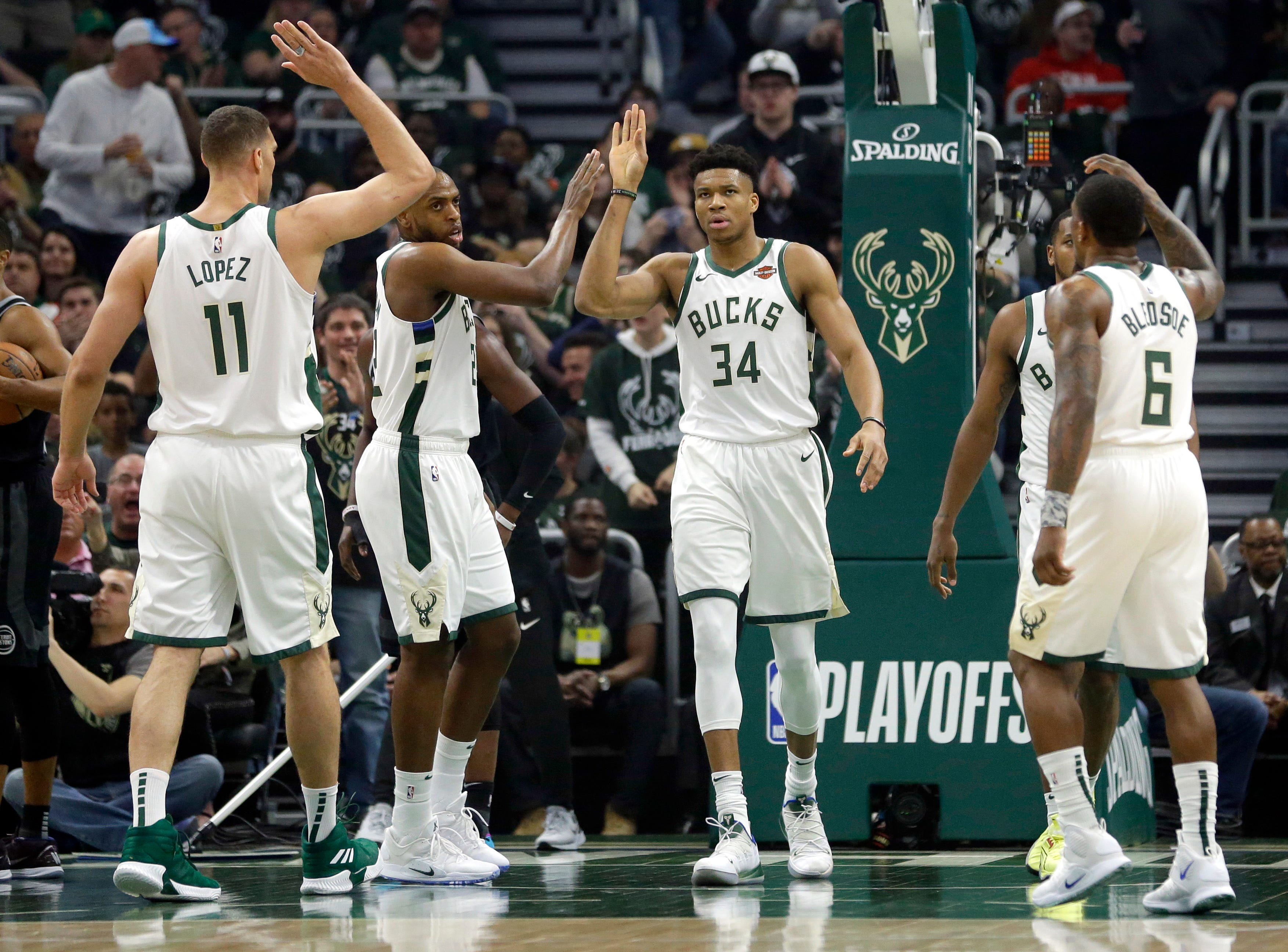 Milwaukee Bucks' Giannis Antetokounmpo gives high-fives to his teammates during the first half of Game 2.