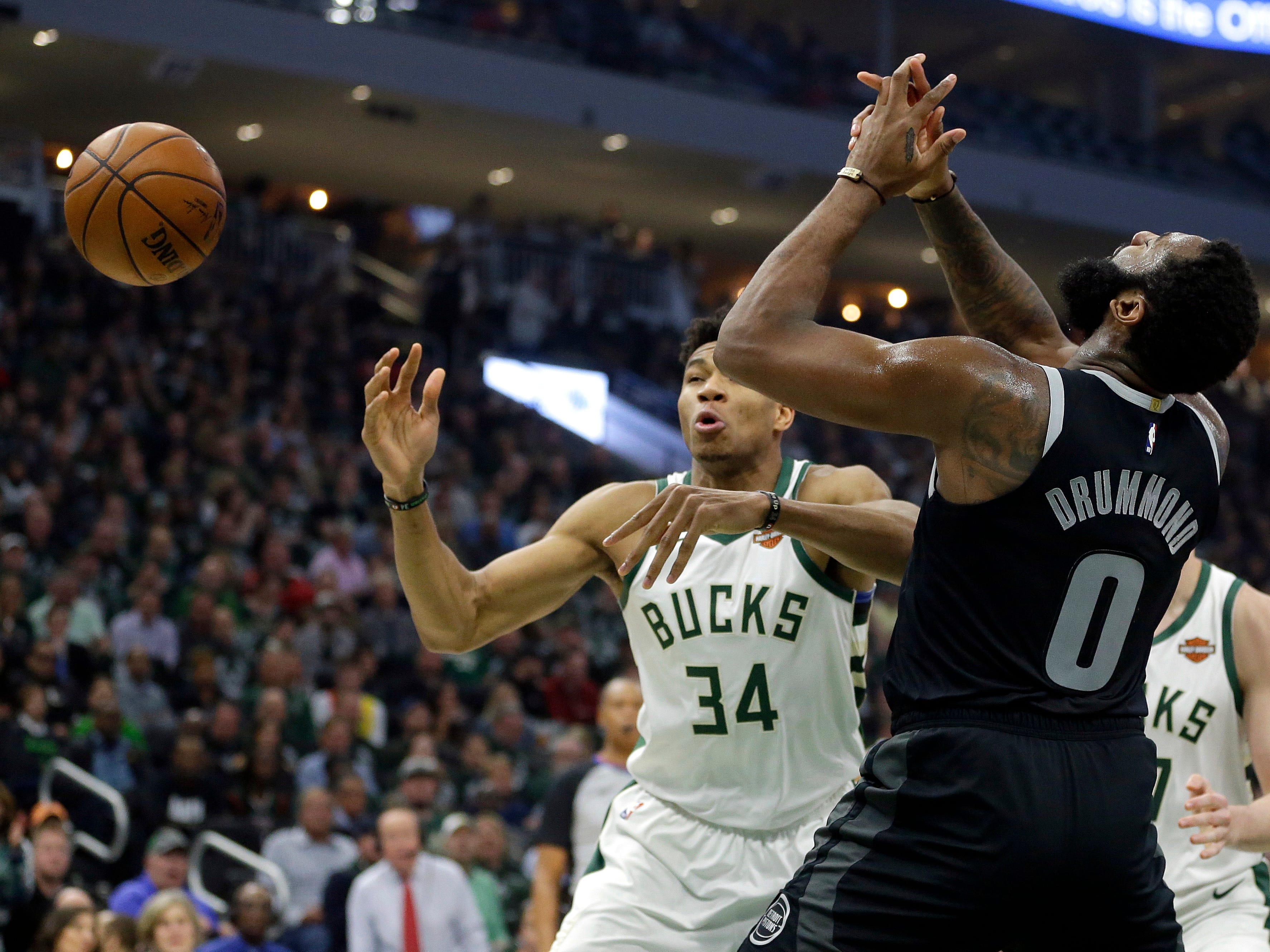 Detroit Pistons' Andre Drummond (0) and Milwaukee Bucks' Giannis Antetokounmpo (34) go for a loose ball during the first half of Game 2.