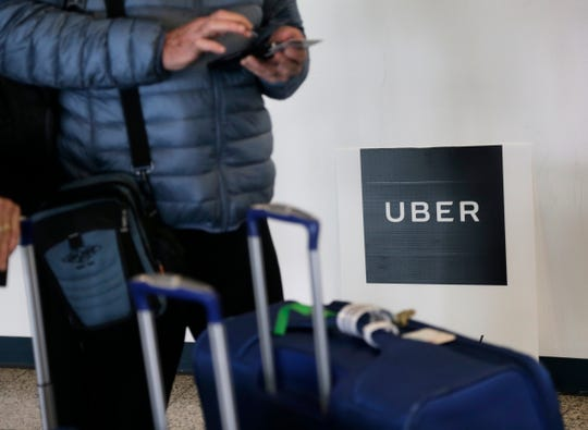 In this March 15, 2017, file photo, a traveler tries to book a ride with Uber at LaGuardia Airport in New York.