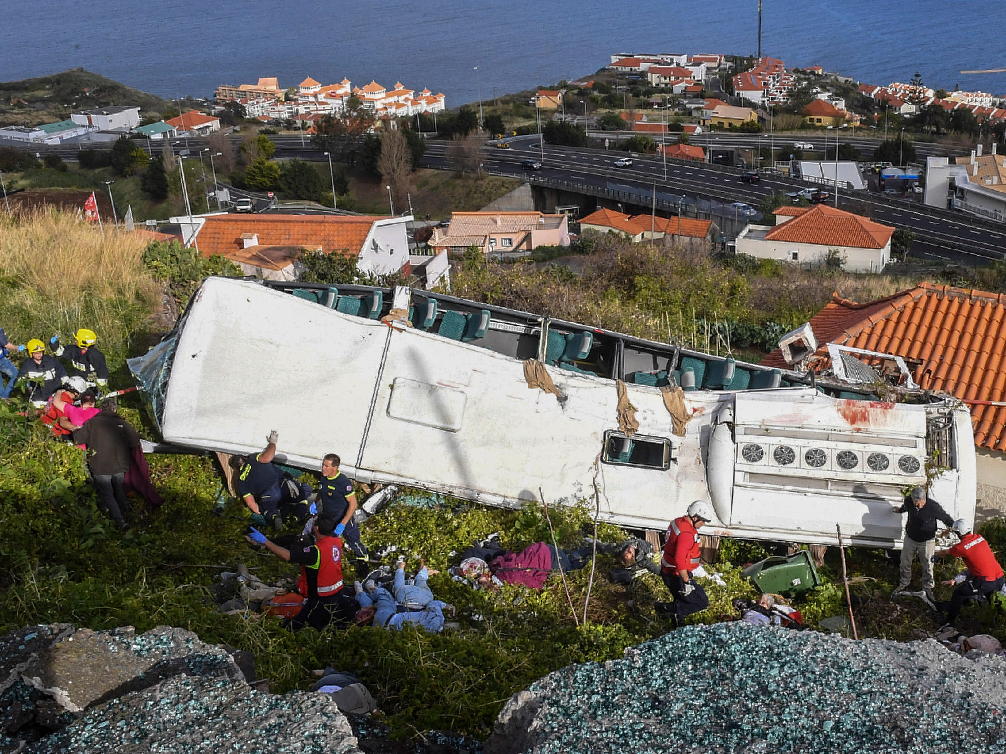 Rescue officials attend the scene after a tour bus crashed in Canico on Portugal's Madeira Island, Wednesday, April 17, 2019. The tour bus carrying German tourists crashed on Portugal's Madeira Island on Wednesday, killing more than a few dozen people and injuring a few dozen others, local authorities said.