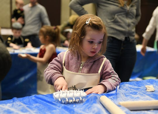 Jade Carlin, 2, of Birmingham uses a roller with spikes to put holes in the matzah dough so that it does not rise while being baked at Matzah Factory Extravaganza at the Jewish Community Center in West Bloomfield on April 14.  The event featured activities designed to help youngsters explore the themes of the Passover holiday.