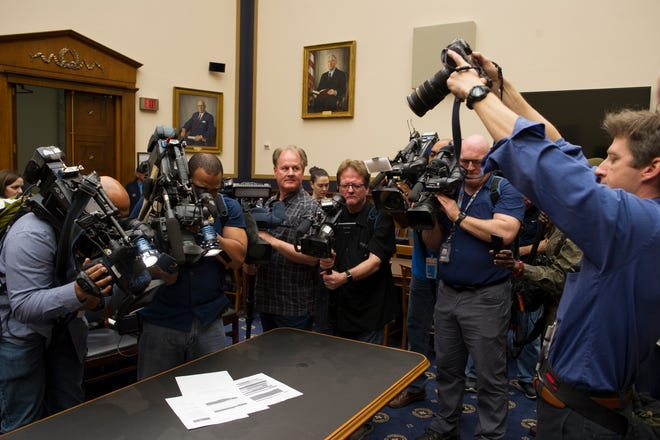 Photojournalists photograph four pages of the Mueller Report laid on the witness table in the House Intelligence Committee hearing room on Capitol Hill, in Washington, Thursday, April 18, 2019.