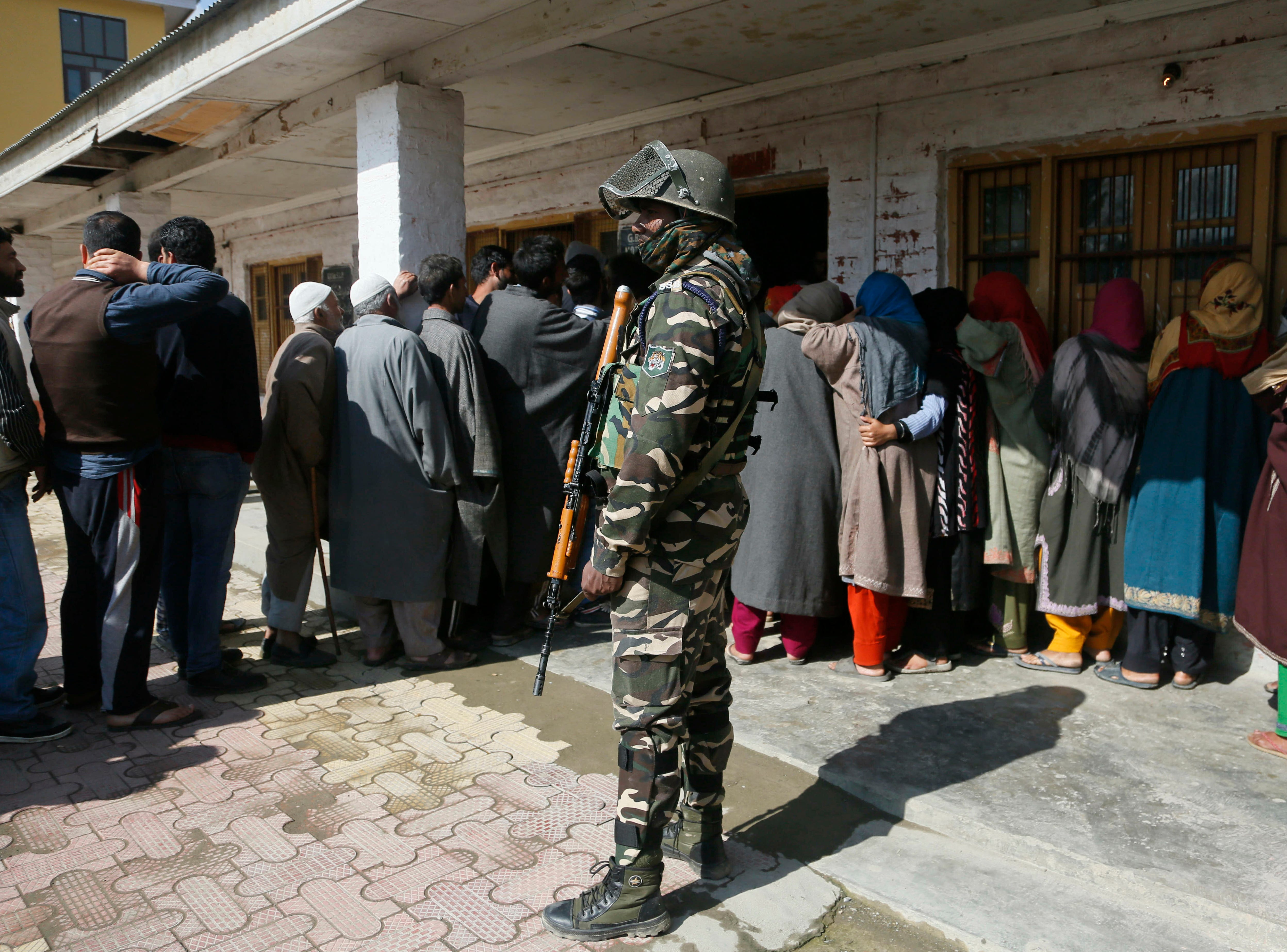 An Indian paramilitary soldier stands guard as Kashmiri voters wait in a queue to cast their votes outside a poling station during the second phase of India's general elections, on the outskirts of Srinagar, Indian controlled Kashmir, Thursday, April 18, 2019. Kashmiri separatist leaders who challenge India's sovereignty over the disputed region have called for a boycott of the vote. Most polling stations in Srinagar and Budgam areas of Kashmir looked deserted in the morning with more armed police, paramilitary soldiers and election staff present than voters.