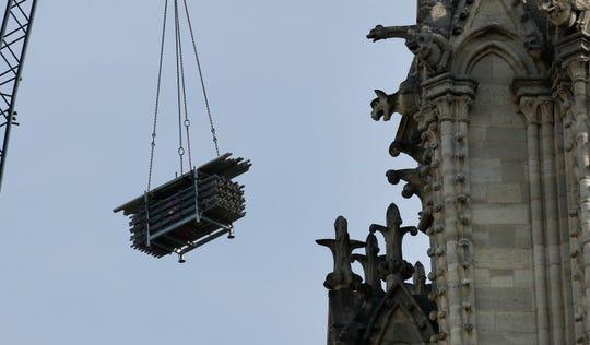 A crane hoists scaffolding past gargoyles outside the Notre Dame Cathedral in Paris, Thursday, April 18, 2019.