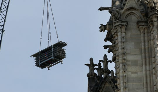 A crane hoists scaffolding past gargoyles outside the Notre Dame Cathedral in Paris, Thursday, April 18, 2019.