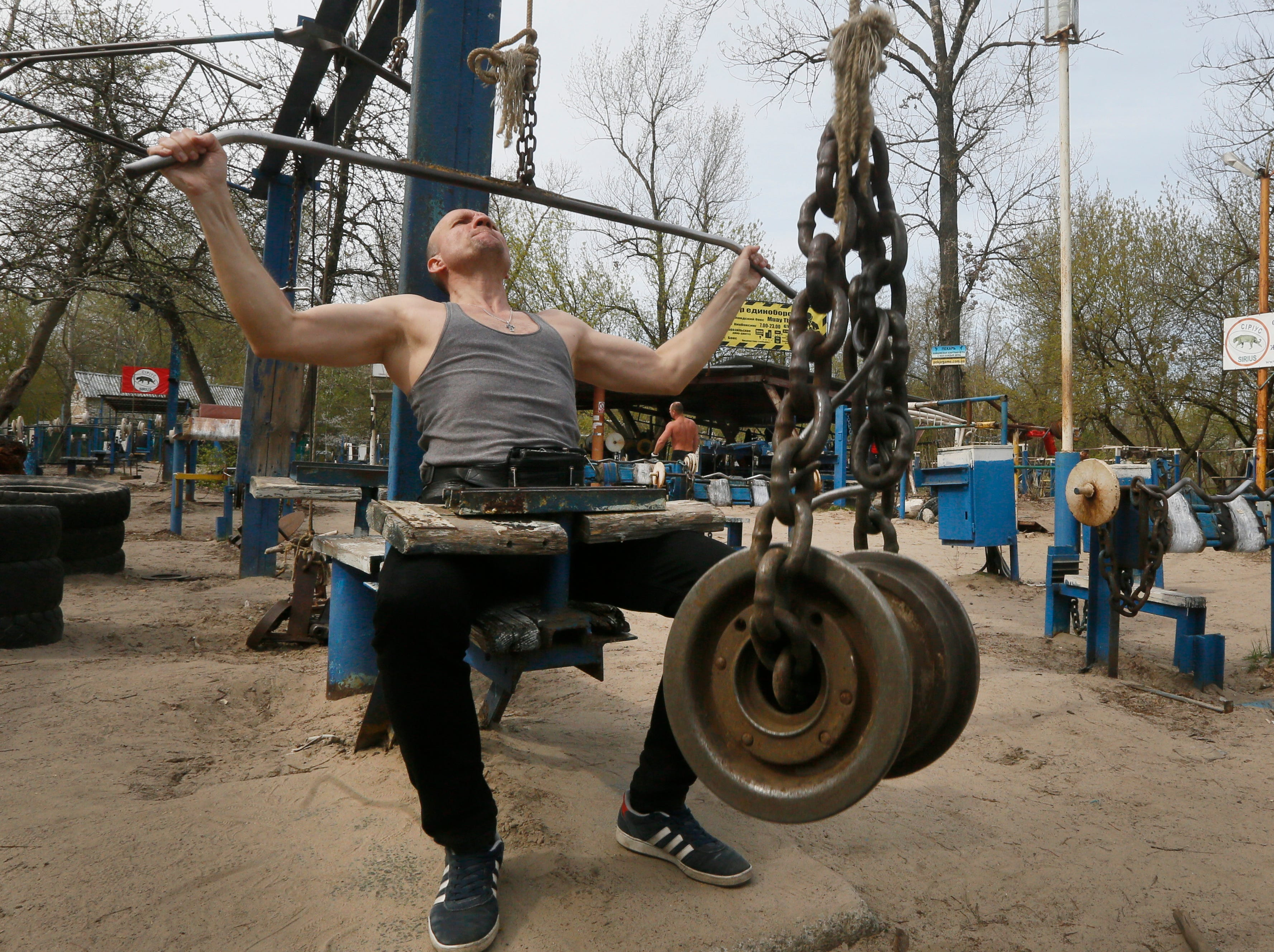 A man lifts metal weights in a scrap metal outdoor gym in a city park on the Dnipro river bank in Ukraine's capital Kiev on Thursday, April 18, 2019.