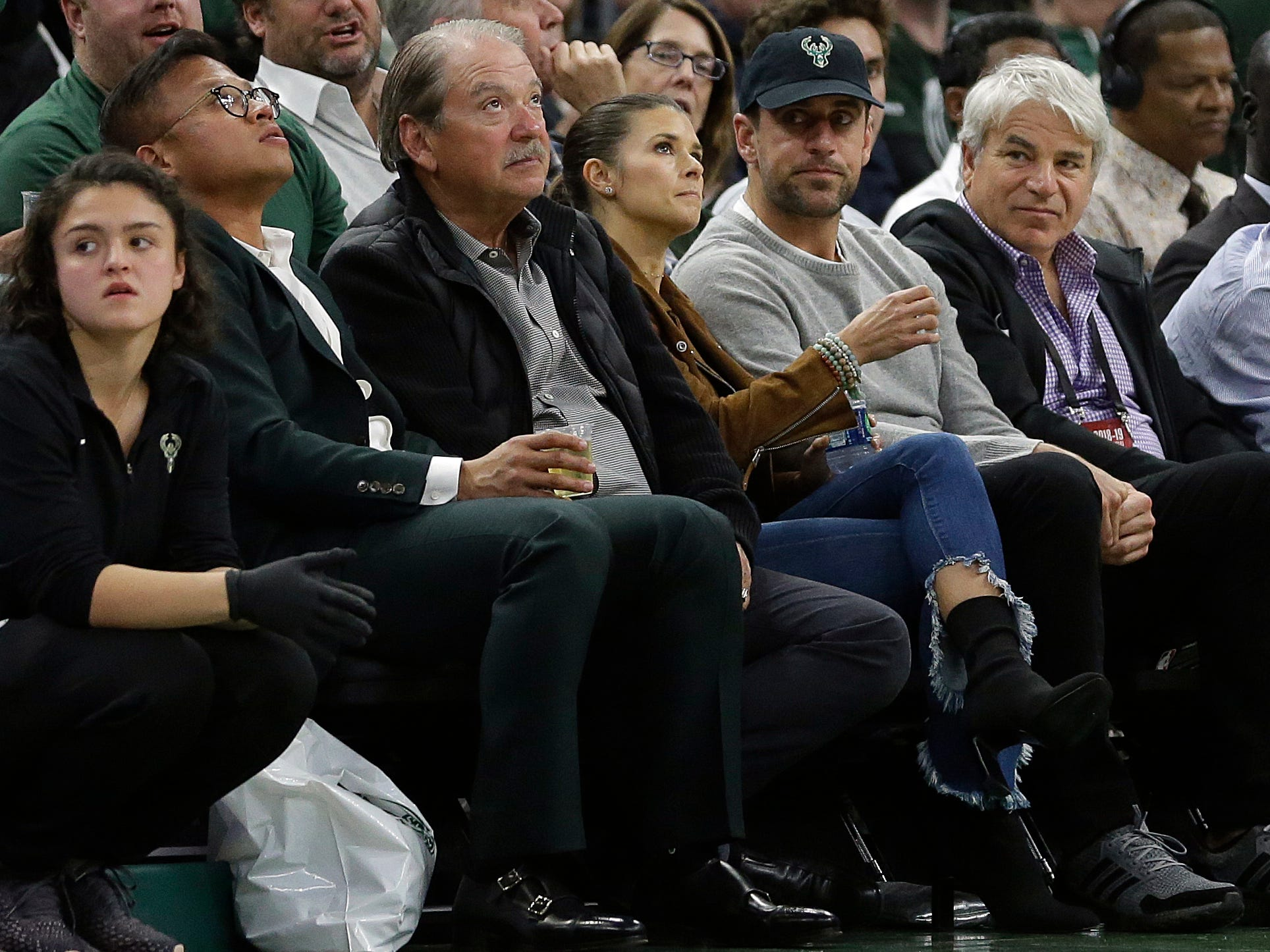 Green Bay Packers quarterback Aaron Rodgers, in black cap, and Danica Patrick watch during the first half.