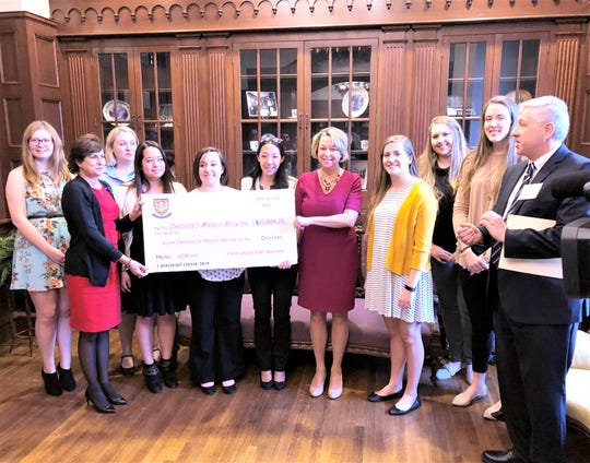 The Elmira College Dance Marathon Team presents a check for $11,609.23 to the Arnot Health Foundation board of directors to support the Children's Miracle Network.