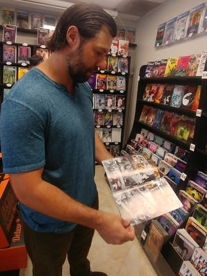 James Haick, of Bonita Springs, flips through a comic at Scout Comics headquarters on April 15, 2019, in Fort Myers.
