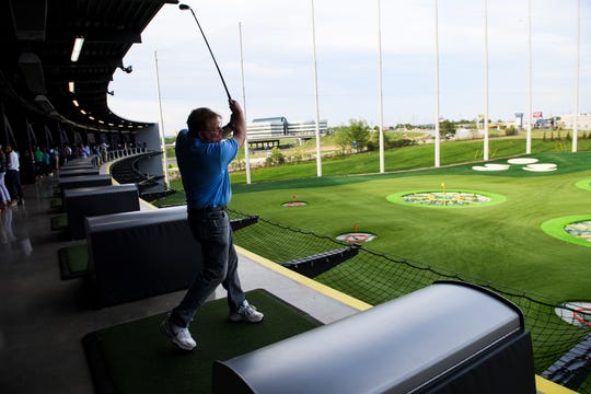 Jeff Hagans hits the ball during a preview day at the new TopGolf location off Pelham Road Wednesday, April 17, 2019.