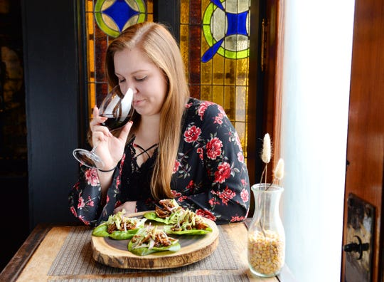 Hannah Lips sniffs a glass of wine before sampling crispy pig ear lettuce wraps with cucumber and red onion slaw at Husk in downtown Greenville.