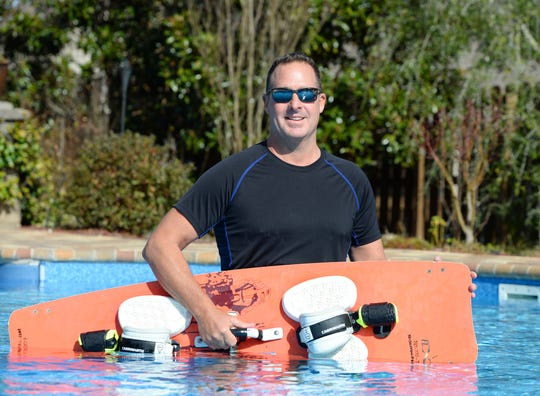Kel Shipman holds his kiteboarding while wading in his home pool.