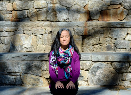 Dr. Maria Cayelli, an integrative health physician, demonstrates how she meditates in a amphitheater at Cancer Survivors Park in Greenville.