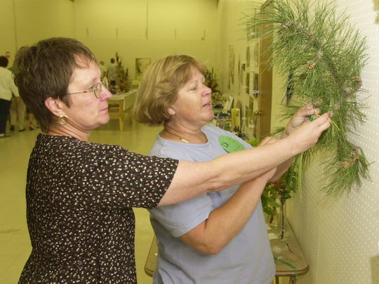Flower show judge Susan Yurman, left, assisted by Pat Eklund, pin a ribbon on a winning entry in the arboreal category on Saturday, June 9, 2001, at the flower show sponsored by the Great Falls Flower Growers, Rainbow Garden Club and Floral Arts club.