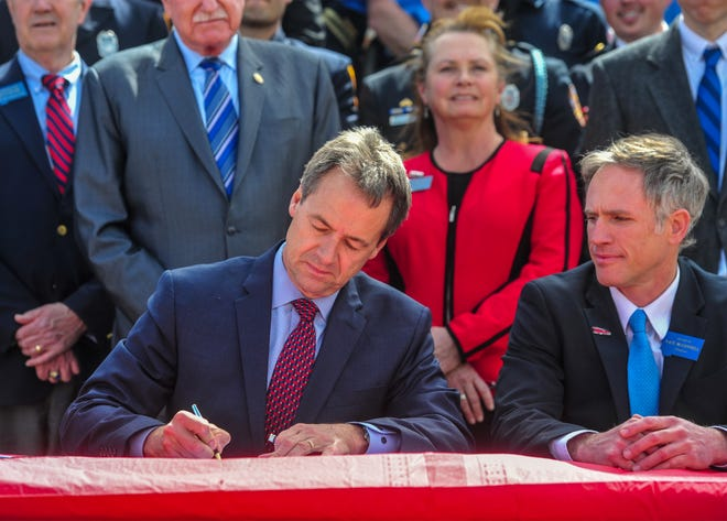 Governor Steve Bullock signs into law Senate Bill 160, the Firefighter Protection Act, on Thursday afternoon on steps of the capitol building in Helena.